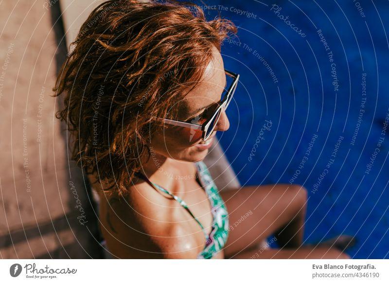 Porträt der schönen kaukasischen Frau sitzt am Pool Seite tragen Bikini-Badebekleidung. Sommerzeit, Urlaub und Lebensstil Kaukasier Schwimmbad Sonnenbrille heiß