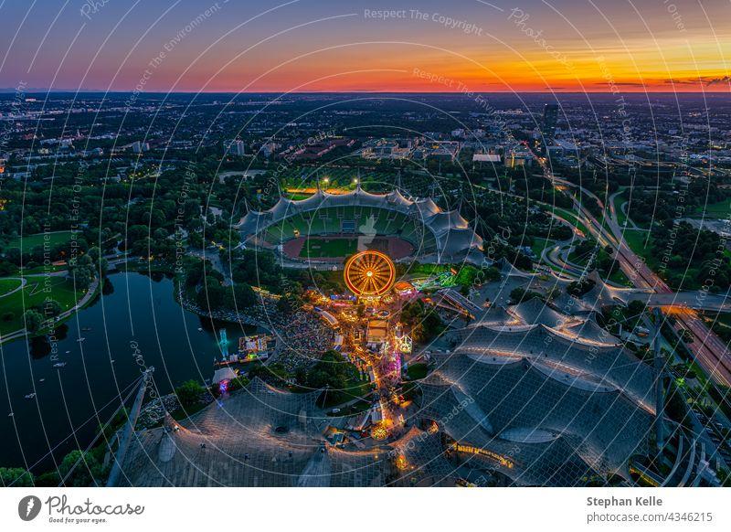 Wunderschöner Münchner Sonnenuntergang aus der Vogelperspektive mit einem Festival im beliebten Olympiapark und dem Stadion in der leuchtend orangen Dämmerung.
