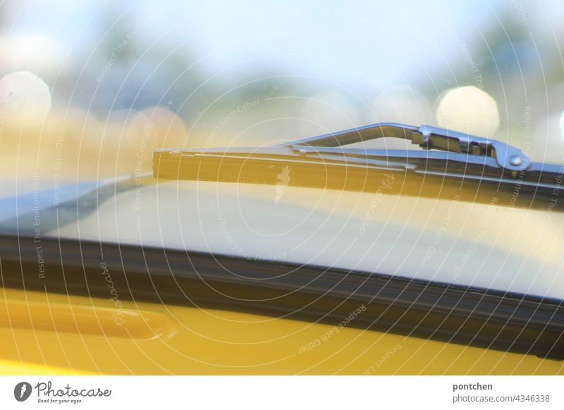 Blick aus dem gelben Auto auf den Scheibenwischer an einem sonnigen Tag. Oldtimer. Frontscheibe. scheibenwischer auto oldtimer autofahren klimawandel ausflug