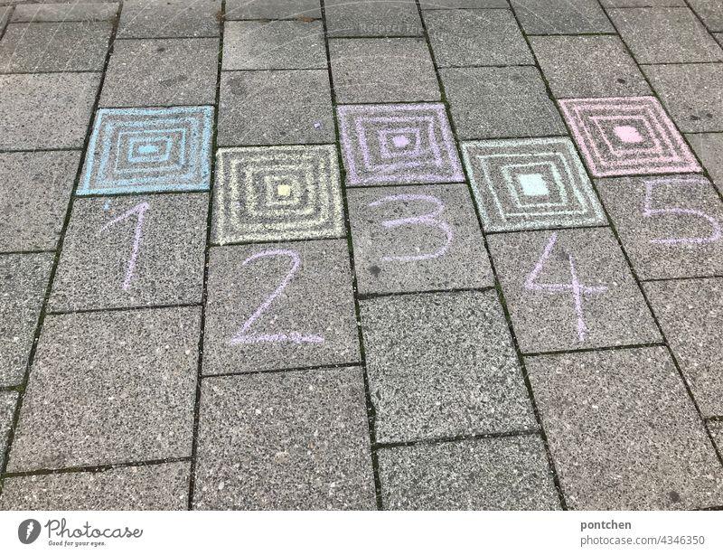1,2,3,4,5 steht mit Straßenkreide auf dem Boden. Kästchenhüpfen,  Kinderspiel, Hüpfspiel. straßenkreide kindheit kästchenhüpfen kinderspiel freude zahlen zählen