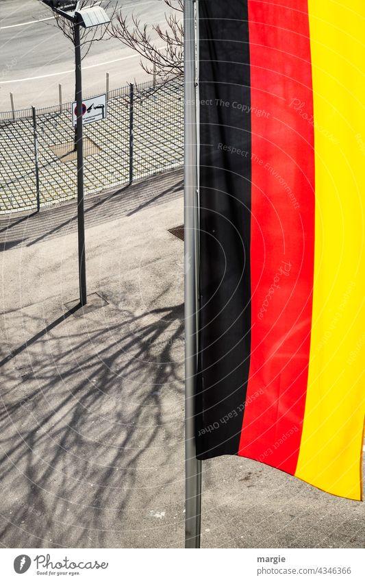 Blick von oben auf eine senkrechte Deutschland Flagge Fahne wehen Außenaufnahme flattern Menschenleer Fahnenmast Zaun Straßenbeleuchtung Schatten Farbfoto