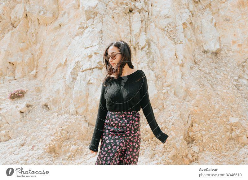 Porträt einer jungen Frau mit einer Sonnenbrille vor einem marmornen Riesenfelsen, Freiheit und Freiheitsbegriff Dame Lächeln Person hübsch genießen Model