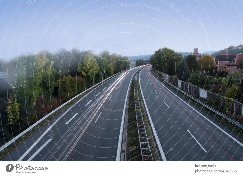 Zweispurige Bundesstraße mit Streifen von Scheinwerferlicht bei Langzeitbelichtung Auto Autobahn B469 Obernburg Elsenfeld Ausfahrt Einfahrt Spur Nebel Abend