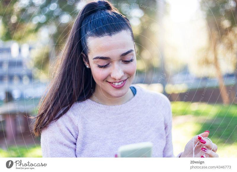 Schönes Mädchen sitzt auf einer Bank Brünette in einer lässigen Kleidung, Mode Lebensstil mit einem Telefon. Attraktive junge weibliche Chatten auf Handy. mit Smartphone