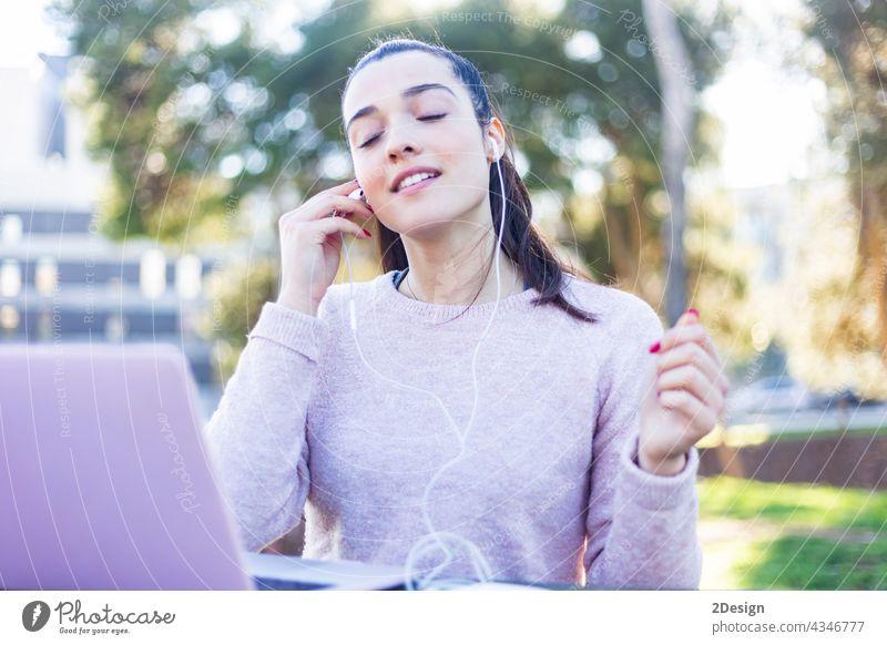 Bild der weiblichen jungen Frau 20s in Freizeitkleidung entspannen im grünen Park, und mit Handy mit Kopfhörern Mädchen Drahtlos Musik benutzend Sitzen