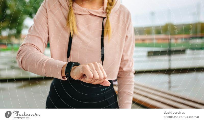 Junge Sportlerin sucht Aktivitätsarmband unkenntlich Frau Athlet Blick smartwatch Mittelteil Textfreiraum Schrittzähler Training Morgen Fitness aktiv attraktiv