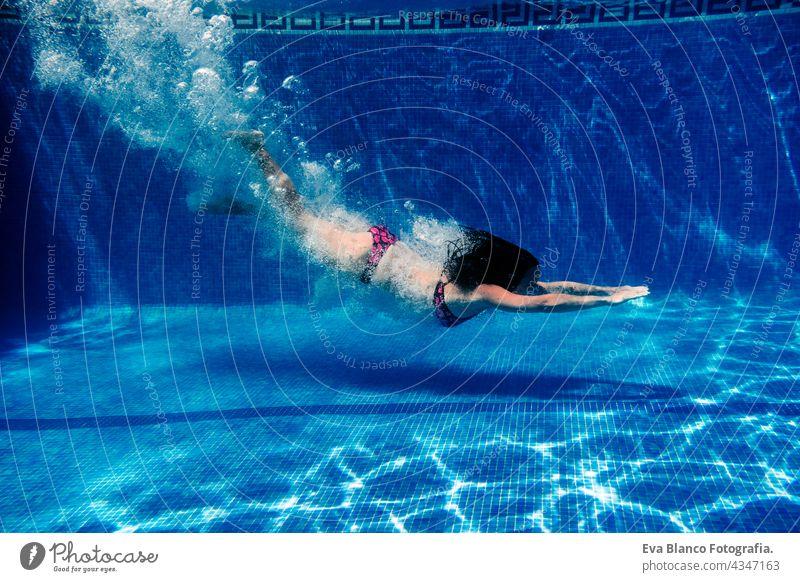 Kaukasische Frau Tauchen im Schwimmbad. Unterwasser-Ansicht. Sommerzeit und Urlaub Konzept unter Wasser Spaß Liebe Blauwasser sonniger Tag im Freien