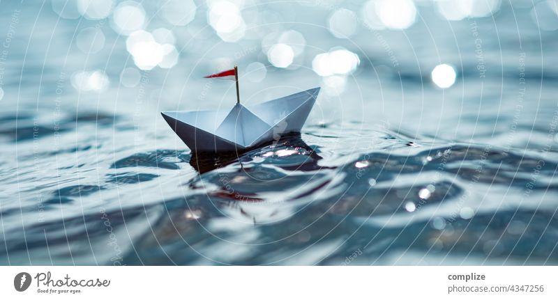 Kleines Papierschiff im Sonnenschein auf dem Meer Freiheit Sonnenstrahlen Sonnenlicht Küste Segelboot Ziel Schifffahrt Kindheit Strand Sommerurlaub Wasser Natur
