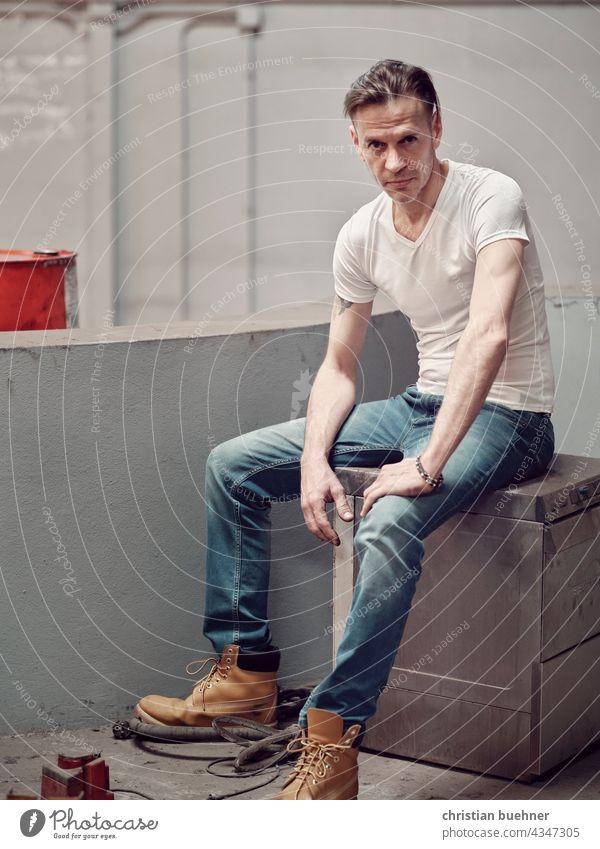 automechaniker in der werkstatt - portrait mann 40 jahre stiefel wekstatt cool sitzend jeans laessig erotisch ernst pruefend interessant dreckige umgebung