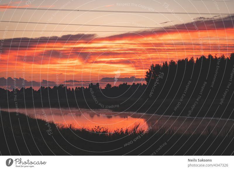 Sonnenuntergang über dem Fluss. Rote orange Wolken. Schwarzer Wald Silhouette über den Fluss. Elektrische Stromleitung Drähte in der Luft. Reflexion von Wolken und Schilf in Fluss macht es orange