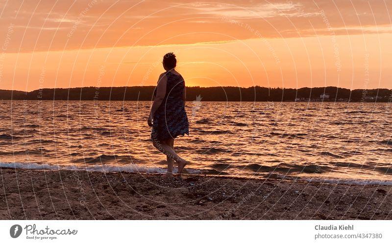 Frau im Kleid spaziert an der Uferlinie des Strandes bei untergehender Sonne Strandspaziergang Strandleben Meer Meeresufer Meerwasser Meereslandschaft uferzone