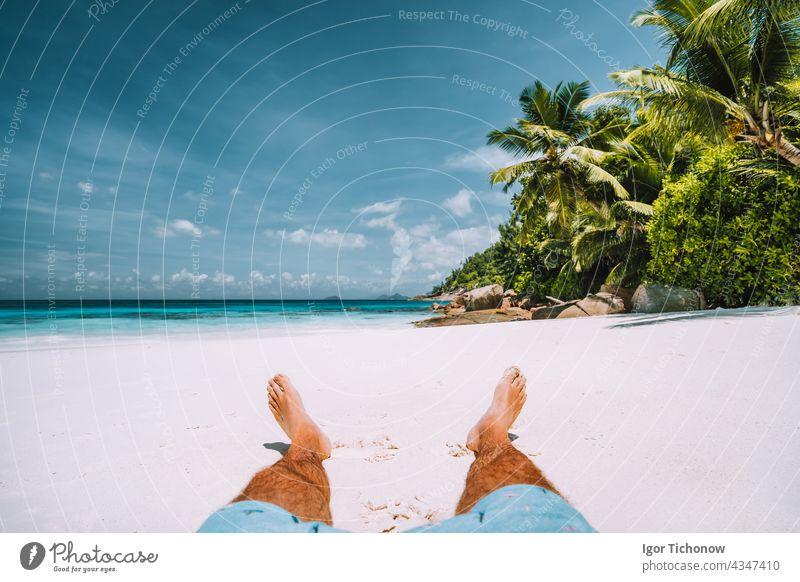 Mann ruht sich am weißen Sandstrand mit schönen Palmen aus Seychellen Strand reisen Urlaub aussruhen tropisch Sonne Sommer Erholung sich[Akk] entspannen