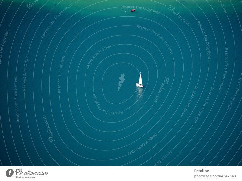 Ein kleines Segelboot segelt treibt still und einsam auf dem Achensee See Urelemente Wasser türkis blau Schiff Bootsfahrt Schifffahrt Menschenleer