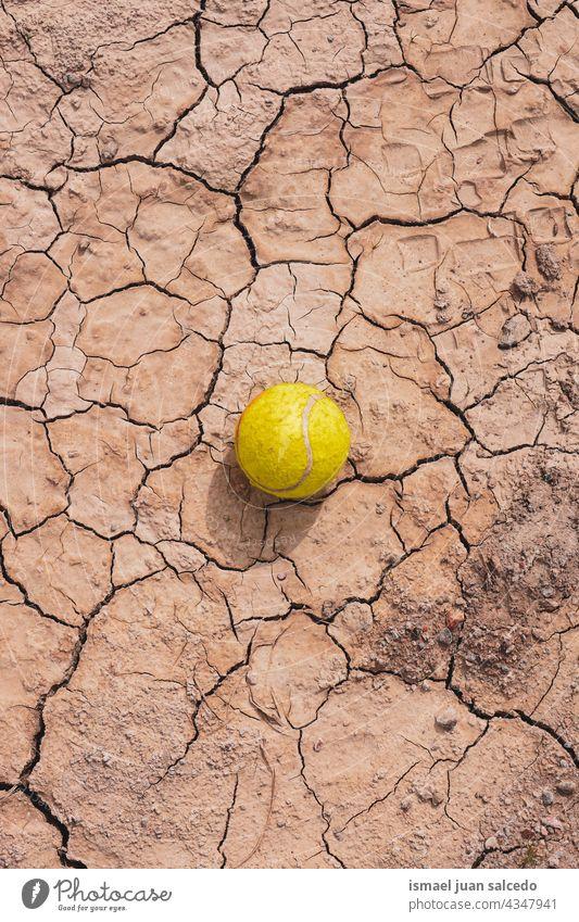 gelber Tennisball auf dem Dessertboden Ball Sport Objekt Stillleben braun alt Verlassen Boden Land trocknen texturiert Erde Natur wüst Klima Muster Schmutz