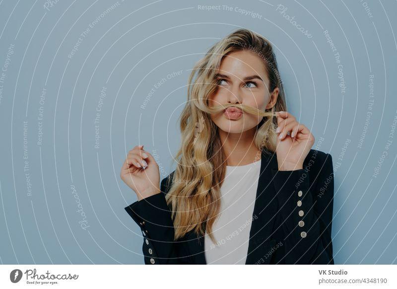 Lustige, fröhliche blonde Frau, die Spaß hat, während sie gegen eine blaue Studiowand posiert und mit einer Haarsträhne spielt lustig freudig Spaß haben