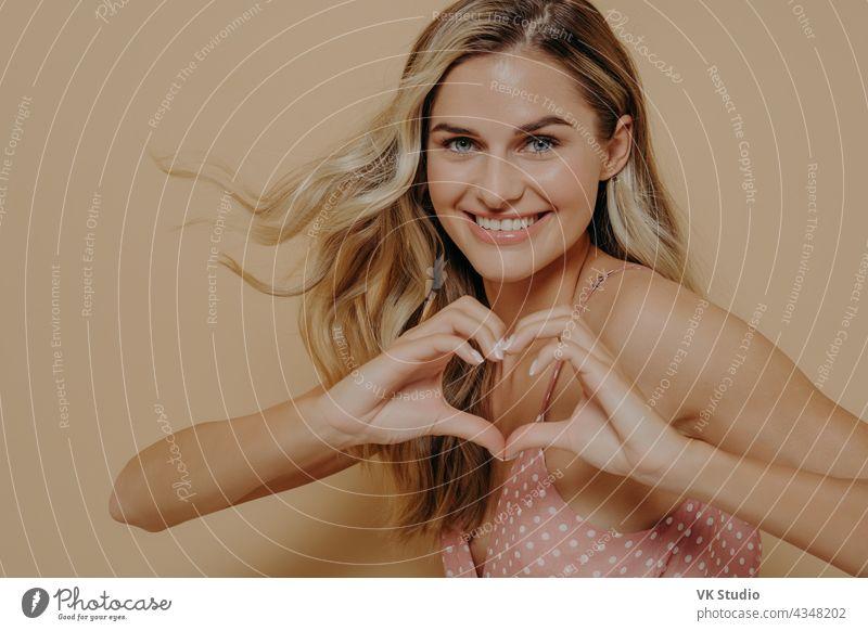 Blonde Frau macht Herzform mit ihren Händen optimistisch blond zeigend gestikulieren Liebe Lächeln anzeigend Zuneigung Angebot Glück Gesicht vereinzelt Ausdruck