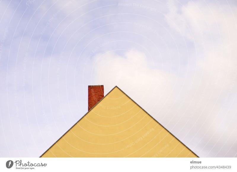 gelbe, fensterlose Giebelwand eines Wohnhauses und roter Ziegelschornstein vor blauem Himmel mit Wolken / wohnen / Dreieck Hausgiebel Schornstein blauer Himmel