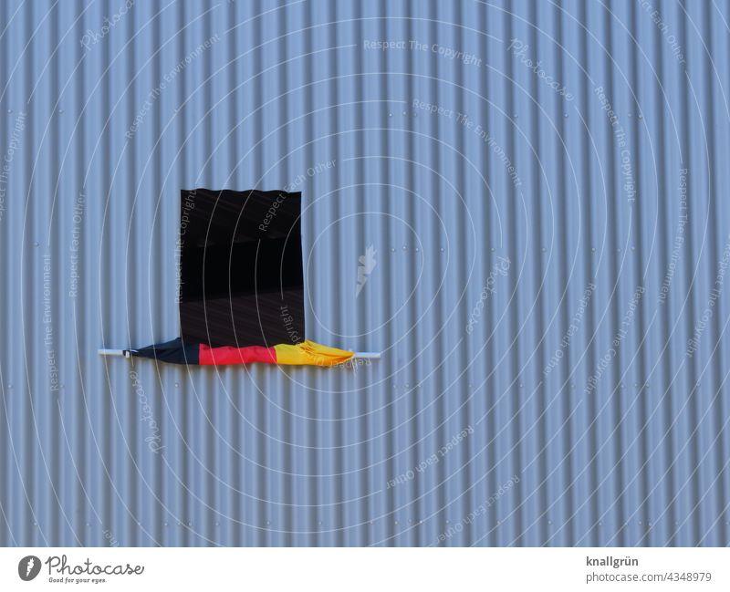 Aufgerollte Deutschlandfahne an einem offenen Fenster aufgerollt Aluminiumfassade Außenaufnahme Farbfoto Menschenleer Architektur Patriotismus Deutsche Flagge