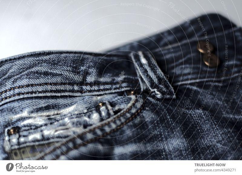 Fast neu, Kult und stylish: Detailaufnahme einer verwaschenen und zerrissenen Bluejeans mit Hosentasche, Gürtelschlaufe und Metallknöpfen Jeans style Mode