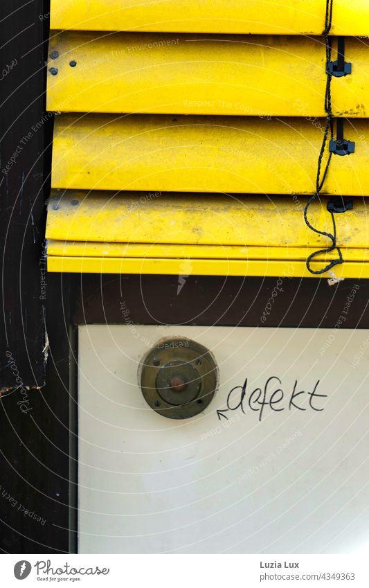 Ein alter Klingelknopf, defekt klingeln Beschriftung Hinweis kaputt Detailaufnahme Fassade Außenaufnahme Nahaufnahme trashig Vergänglichkeit gelb Rollo Jalousie