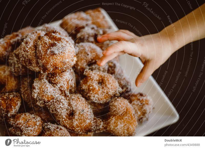Eine Hand greift nach Pfannkuchen | Quarkbällchen | Prilleken | Krapfen | Karnevallsgebäck süß lecker Lebensmittel Dessert Ernährung Farbfoto Süßwaren Gebäck