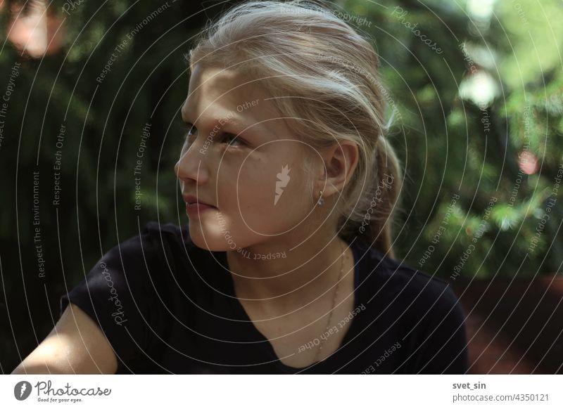 Ein blondes Teenager-Mädchen in einem schwarzen T-Shirt sitzt im Freien im Grünen und schaut interessiert weg. Porträt eines hübschen blonden Mädchens im Halbprofil mit Sonnenblendung im Gesicht.