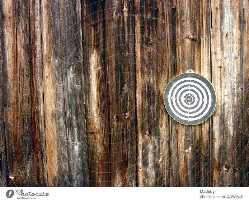 Runde Dartscheibe für das Dartspiel auf dem braunen Holz der Fassade einer alten Scheune auf einem Bauernhof in Rudersau bei Rottenbuch im Kreis Weilheim-Schongau in Oberbayern