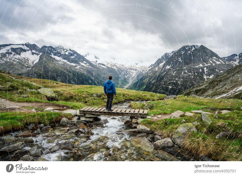Wanderer rastet auf einer kleinen Brücke über einen Gebirgsfluss am Schlegeis See, Zillertaler Alpen, Österreich schlegeis stausee schön wandern tirol reisen