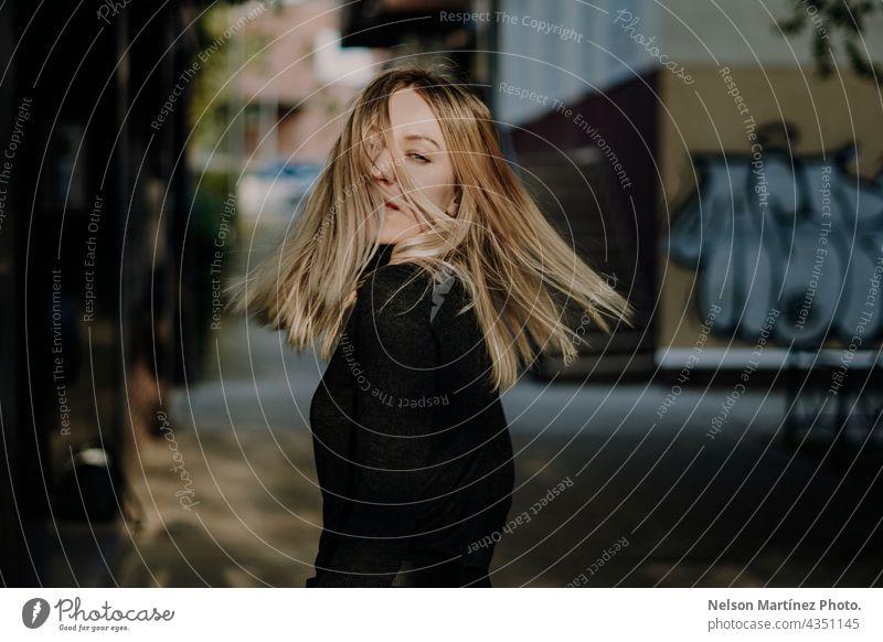Porträt einer schönen blonden kaukasischen Frau bewegt ihr Haar Kaukasier urban Stil selbstbewusst Lifestyle attraktiv jung Mädchen Mode Menschen Straße lässig