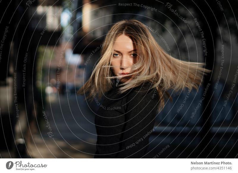 Porträt einer schönen blonden kaukasischen Frau bewegt ihr Haar Stil kausal Lifestyle Kaukasier Straße urban attraktiv jung Mode Außenaufnahme lässig Mensch