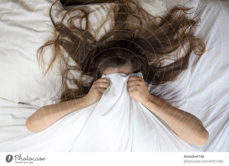 Junge Frau, die im Bett liegt und leidet, müde Frau, die ihr Gesicht mit den Händen bedeckt, kann nicht schlafen und fühlt sich erschöpft auf weißen Laken im Schlafzimmer