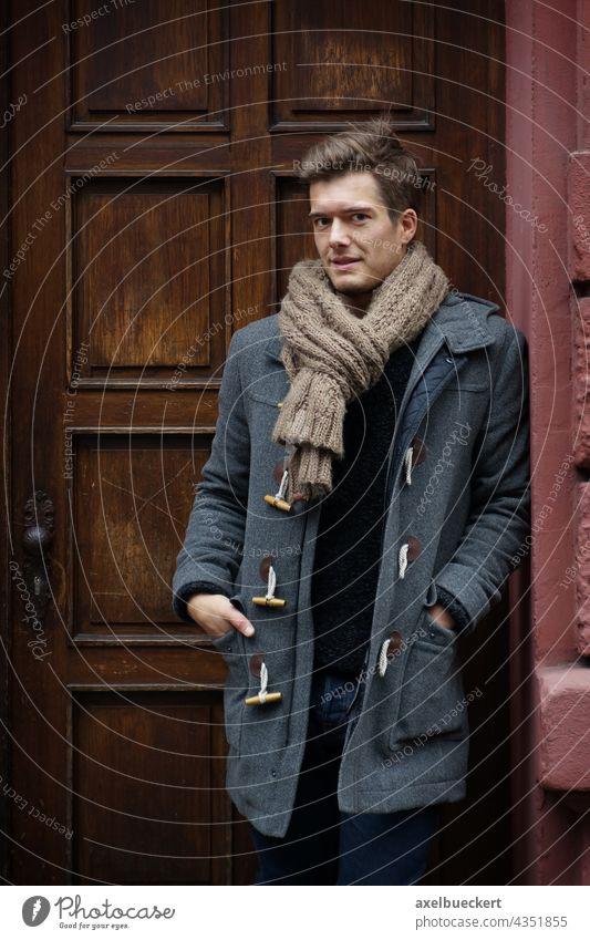 junger Mann mit Dufflecoat wartet im Hauseingang Junger Mann warten Haustür Winter dufflecoat Mantel winterjacke Schal blond stehen anlehnen Blick in die Kamera