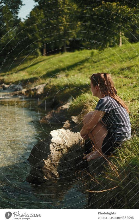 Junge Frau sitzt am Ufer eines kleinen Flusses und schaut in die Ferne Kontrast Schatten Außenaufnahme Farbfoto Vertrauen Glück sitzen genießen Bach Erholung