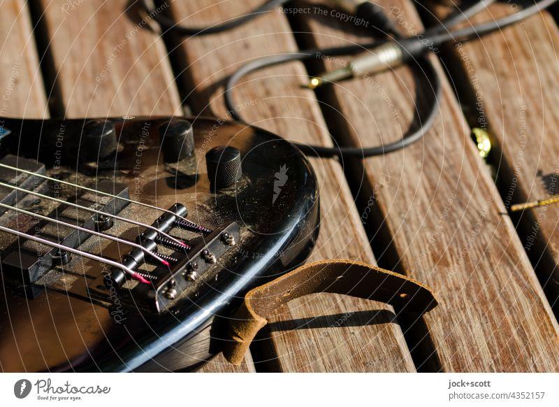 Straßenmusik mit E-Gitarre + Audiokabel im Detail Musikinstrument Saite Saiteninstrumente Detailaufnahme Freizeit & Hobby Drehregler Sonnenlicht Parkbank
