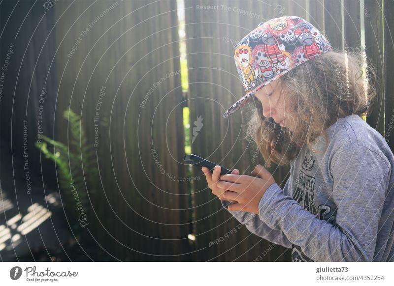Teenager Junge mit coolem Basecap, online, draussen in sein Handy vertieft Porträt Blick nach unten Zentralperspektive Schwache Tiefenschärfe Gegenlicht