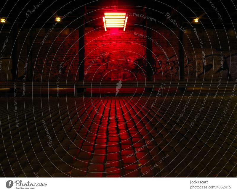 Dunkler Tunnel durch rotes Neonlicht beleuchtet Verkehrswege Straße Wand dunkel leuchten Lichtinstallation Beleuchtung Kopfsteinpflaster Säule Straßenkunst