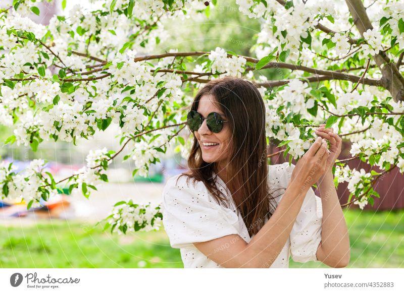 Attraktive und schöne junge Frau mit Sonnenbrille. Junge Frau kaukasischen Ethnizität. Lächelnd und glücklich weiblich ist in weißer Kleidung posiert. Fröhlich hübsche Frau auf blühenden Apfelbaum Hintergrund.
