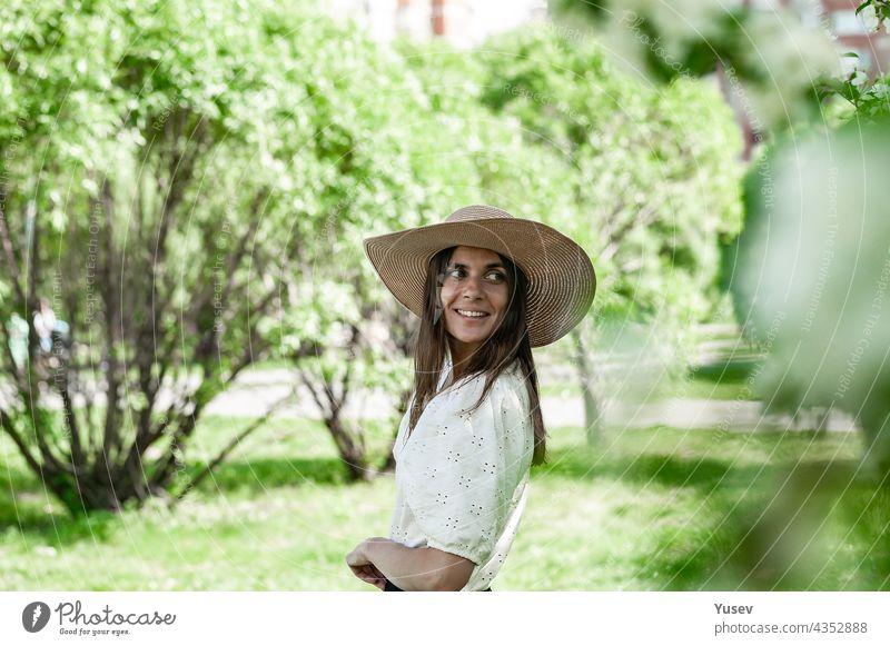 Porträt hübsche und attraktive Frau in einem Strohhut. Junge Frau in auf einem Frühling Park Hintergrund. Nette lächelnd und glücklich junge Frau. Schönes Modell auf der weißen Bluse. Lebensstil
