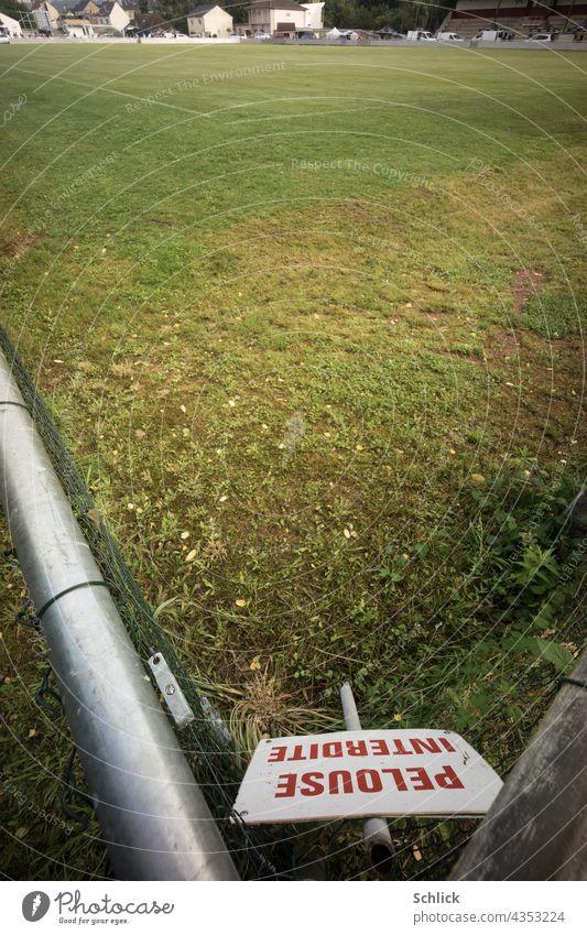 Schild mit roter Aufschrift PELOUSE INTERDITE Rasen betreten verboten steht in der Ecke eines Fußballplatzes französisch Frankreich Schrift Rasenplatz Winkel