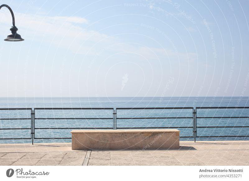 Steinbank auf einer Seebrücke an der italienischen Küste im Morgenlicht horizontal im Freien Farbbild farbenfroh niemand keine Menschen Himmel blau Hintergrund