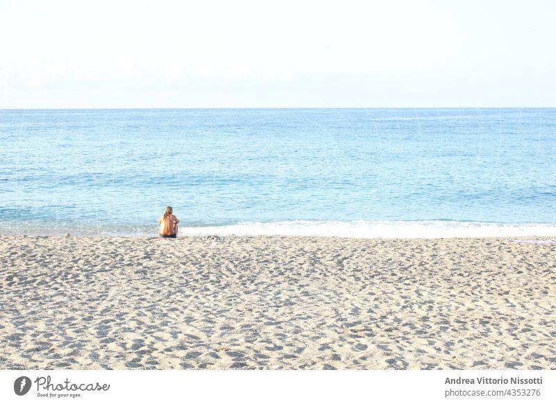 Frau, die allein am Strand sitzt und das Meer betrachtet, mit Platz für Ihren Text horizontal Farbbild Menschen Kaukasier im Freien MEER Seeküste Sommer