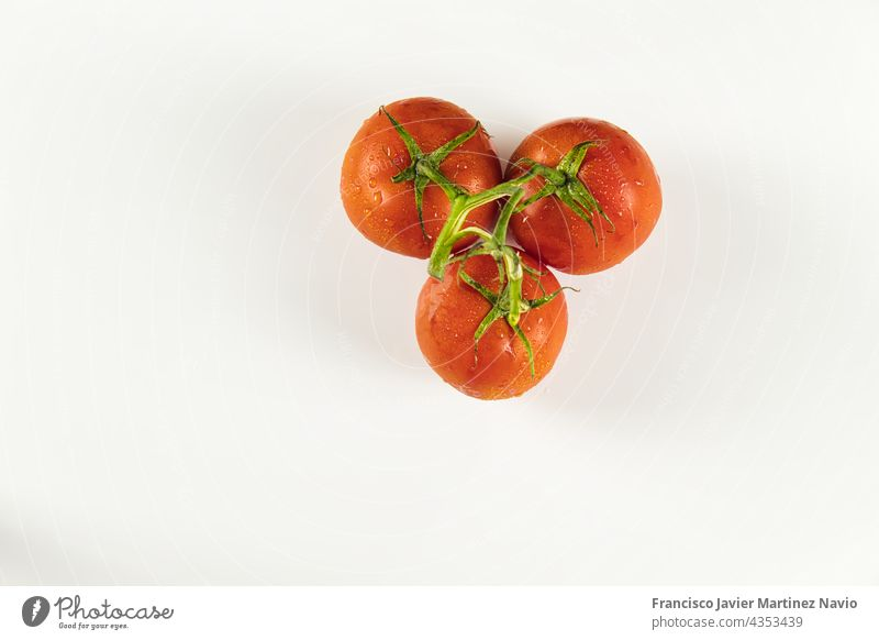 Draufsicht auf eine Tomatentraube mit Tropfen auf weißem Hintergrund rot Textfreiraum Cluster 3 Haufen oben reif kreisen Nährstoffversorgung Diät Objekt
