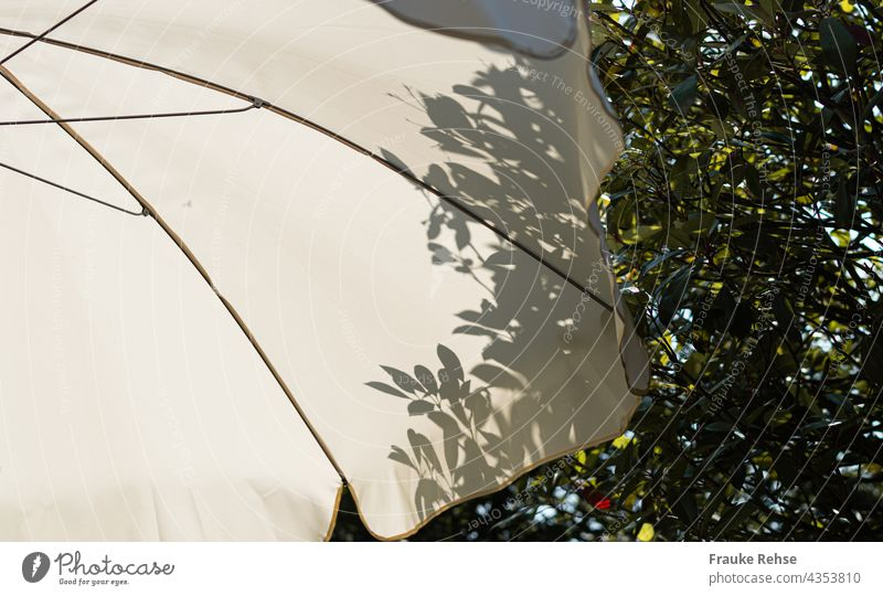Teil eines weißen Sonnenschirms mit Schatten von Blättern eines Baumes hinter ihm sonnig Sommerstimmung Garten im Schatten Licht Schattenspiel Kontrast