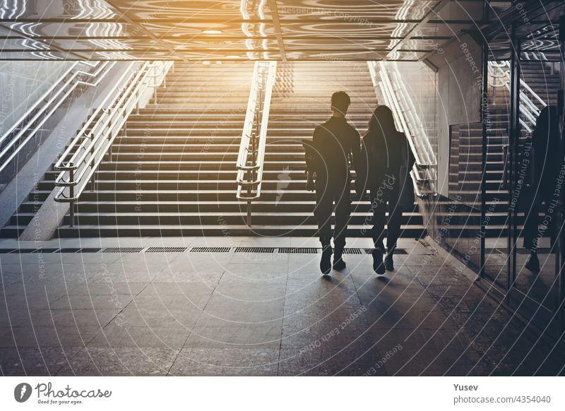 Silhouetten von Menschen. Menschen in unterirdischer Kreuzung. Blick von hinten. Pärchen von jungen Leuten auf dem Zebrastreifen. Das Paar hält sich an den Händen und geht durch die Stadt. Unbekannte Personen. Straßenfoto