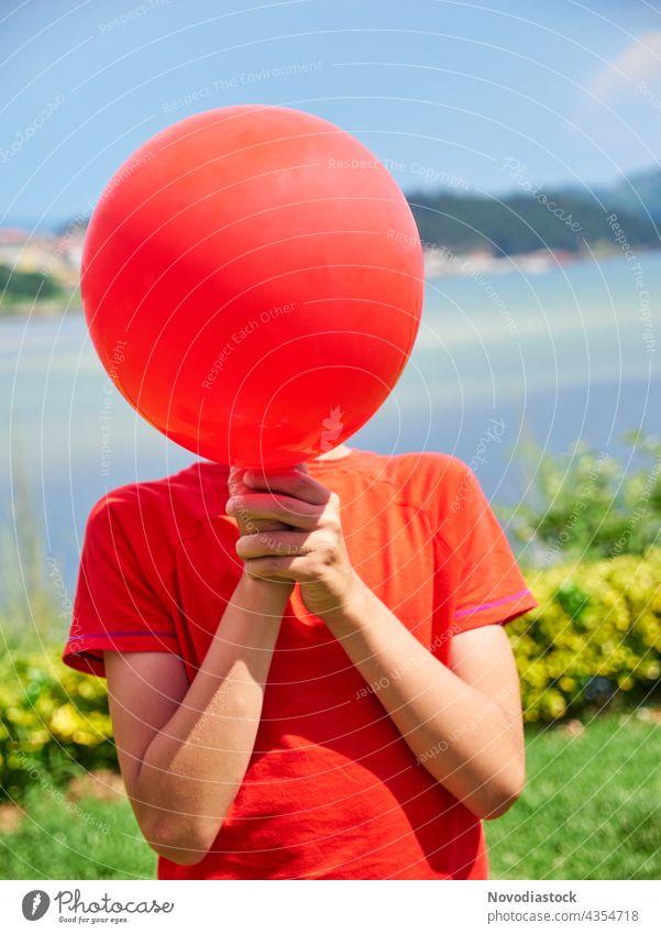 Junge versteckt sein Gesicht hinter einem roten Luftballon allein Hintergrund Geburtstag lässig Freizeitbekleidung Kaukasier feiern Feier Kind Kindheit