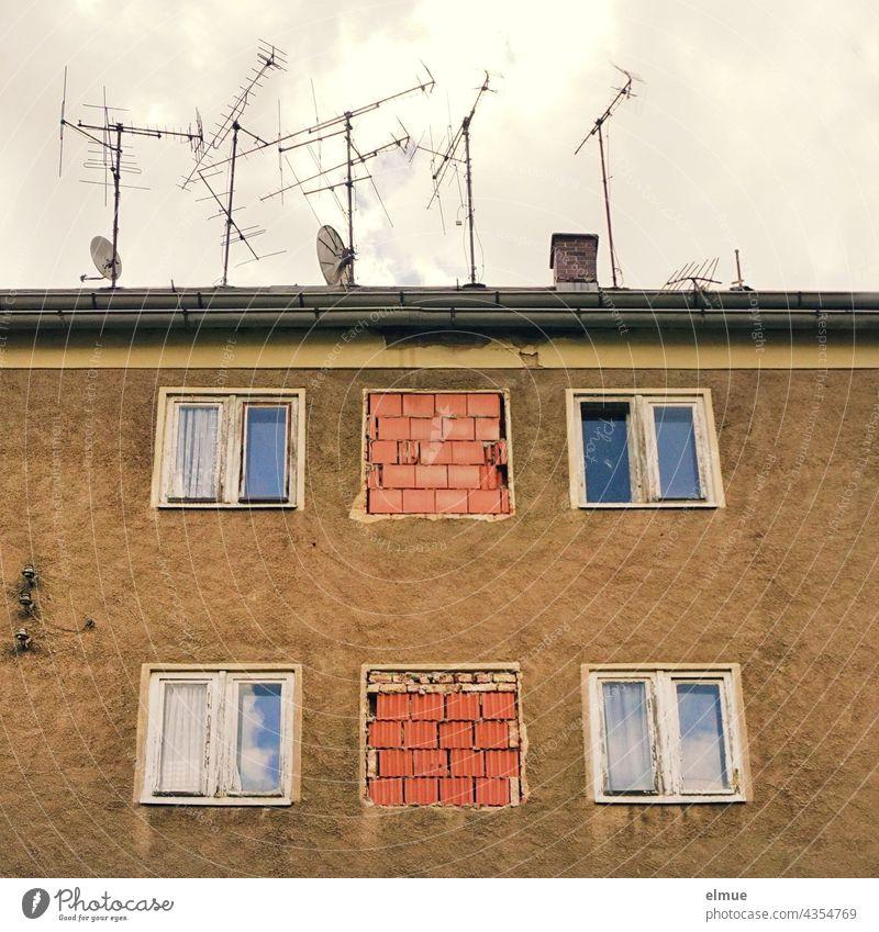 Blick auf ein altes, unbewohntes Mehrfamilienhaus mit Fenstern, zum Teil zugemauert, und zahlreichen alten Fernsehantennen sowie Satellitenschüsseln auf dem Dach / marode / Kernsanierung / Immobilie