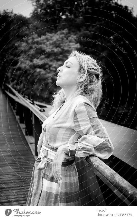 blonde Frau lehnt an einer Brücke II Porträt Kleid Natur Baum Park Garten romantisch Außenseite San Sebastián fshion niedlich Menschen reif im Freien Lifestyle