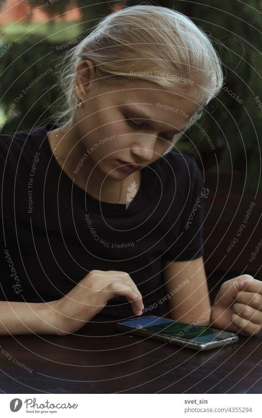 Ein blondes Teenager-Mädchen in einem schwarzen T-Shirt sitzt im Freien an einem Holztisch und blättert (liest) auf ihrem Smartphone durch Beiträge in sozialen Netzwerken.