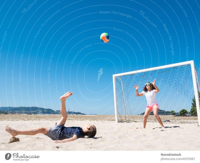 zwei Kinder spielen Fußball am Strand Glück Wasser heiter Freundlichkeit Ufer Meer Sommer lässig MEER Zusammensein Freude Nähe Lächeln Urlaub Sport kurzweilig