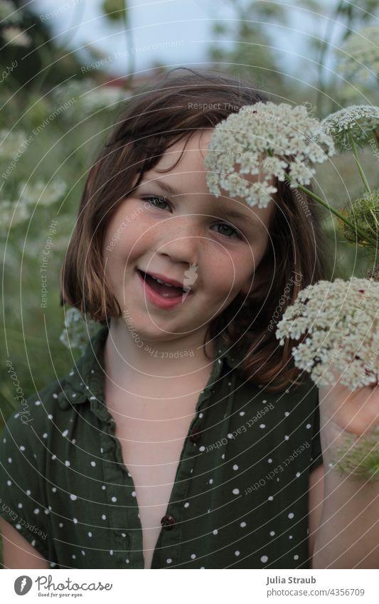 Mädchen steht mitten in der Blumenwiese Doldenblütler Wilde Möhrenblüte Färberkamille Schierling beobachten schauen braune Haare kurze haare stehen sommerbräune